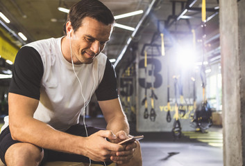 Portrait of beaming male listening music in headsets while typing in mobile after training in gym