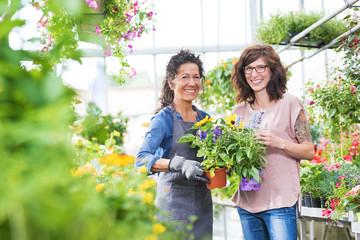 Verkäuferin und Kundin im Gartencenter lächeln fröhlich in die Kamera