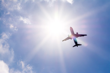 The plane flies in the sky against the sun.