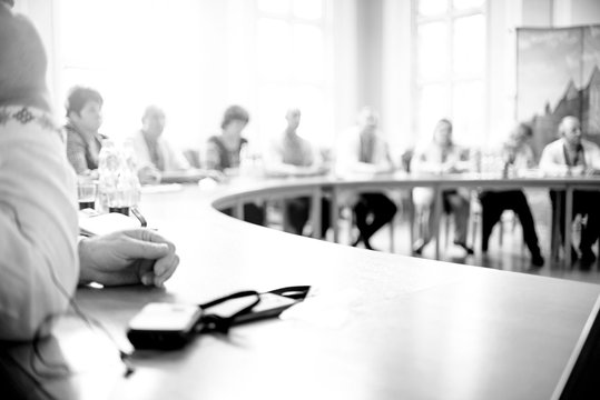 People at a round table discuss different issues. B/W photo. The photaography is blurry