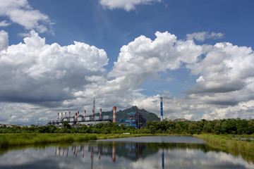 White fluffy clouds in the blue sky and Power plant background