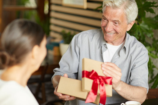 Happy senior man opening giftbox with present from his wife and looking at her