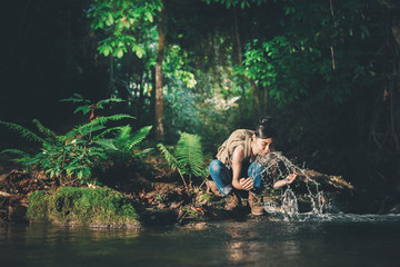 Young hiking lady washing her hands in the fresh cool water of a mountain stream.