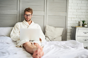 Full length portrait of busy man working at laptop in morning. He is sitting on bed in bathrobe and holding computer on knees while looking precisely in glasses at screen