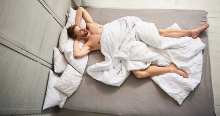Top view of young male relaxing in bed. He is lying on back with folded hands covered by white linens and slumbering