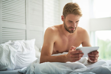 Smiling handsome man sitting on linens in morning and using tablet. He is watching at screen with delight enjoying leisure in apartment