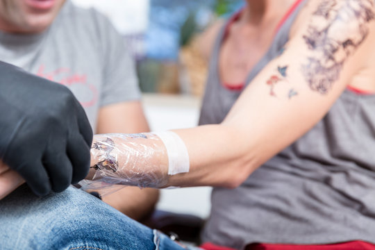 Close-up of the wrapped forearm of a young woman after getting a new cool tattoo in a modern studio with sterile safety supplies