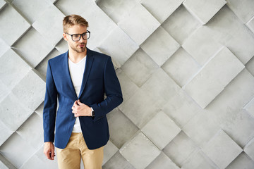 Waist up portrait of male standing and touching jacket. He is wearing eyeglasses and looking sideways confidently. Copy space in right side