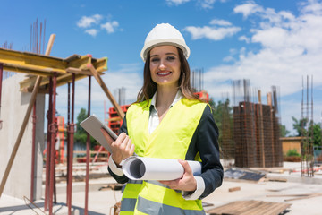 Portrait of a confident female architect or engineer with can-do attitude smiling while holding a rolled blueprint and a tablet on the construction site