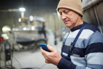 Mature engineer in workwear messaging or reading notification in smartphone