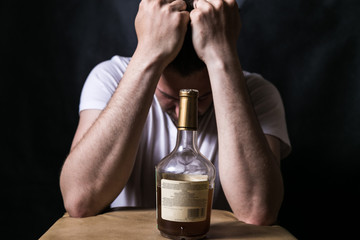 bottle of alcohol with drinking man. Serious unhappy sad man sitting. alcohol addiction. social problems