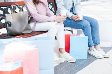 Two girls in jeans and jackets sitting on bench, having drinks after shopping and discussing their purchases