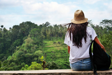 A woman sitting on a wooden bench admires the fantastic landscape in front of her and the nature that surrounds her after a big walk. Concept of adventure, vacation and travel.