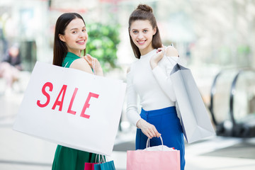 Two cheerful friendly girls in smart casual looking at you with smiles after successful shopping in the mall