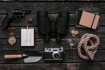 Compass, binoculars, film photo camera, loupe, handgun, diary book, shovel, rope, hat and gold ore on adventurer or explorer wooden table. Traveler equipment.