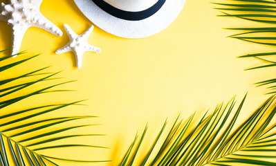Tropical palm leaves, hat, starfish, seashells on yellow background. Travel vacation concept. Summer background. Flat lay, top view, copy space