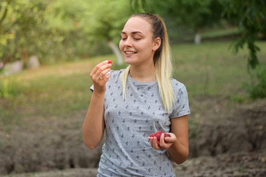 Happy young girl in gray t shirt eating raspberries outside on the green background.