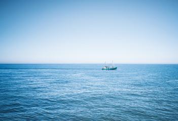 fishing vessel on wide blue ocean against clear sky