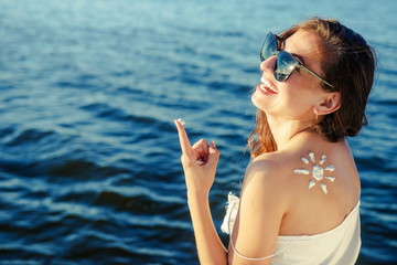 Portrait woman on  sea background. Sunbath protection. Woman using sun cream on the beach. Sun on a girl's shoulder