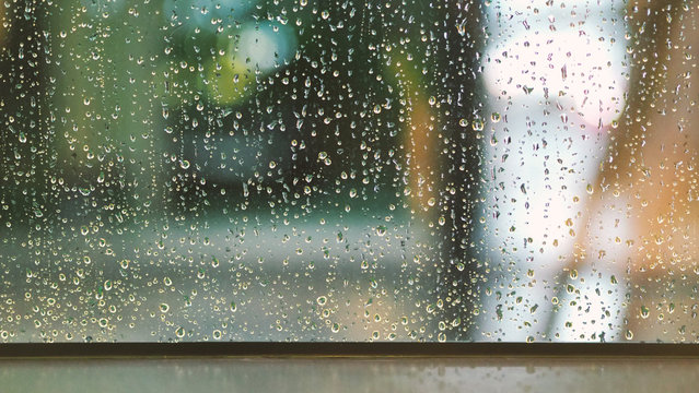 Raindrops texture on the glass window frame of cafe room and nature background in rainy season
