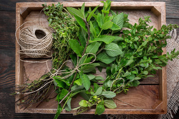 Mixed fresh summer herbs in wooden rustic box, overhead view, close up