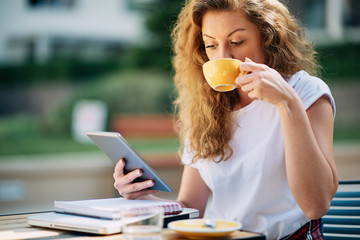 Female student using tablet and drinking coffee in cafe. Books and notebooks on a table.
