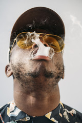 Black stylish man wearing sunglasses. He is vaping with an electronic cigarrete outdoor