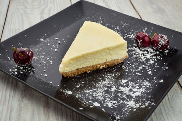 Classic New York cheesecake with berries on black plate. Dessert concept