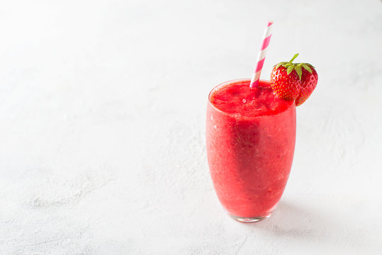 Strawberry smoothie and fresh raw berries on white background