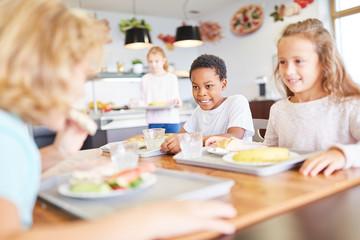 Glückliche Kinder essen in der Kantine