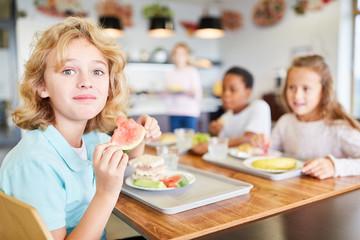 Junge in der Kantine beim Mittagessen