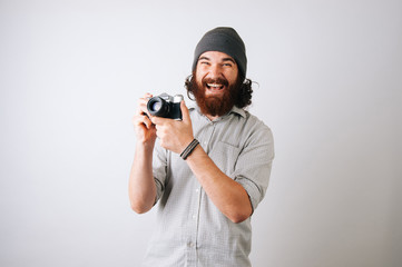 Excited man holding a camera in his hand wearing a plaid shirt and a fur cap hat on a white background. Young bearded man smiling at the camera. Photography courses concept.