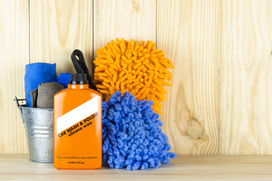 Car wash equipment or car cleaning product such as   brush with mitts and microfiber tank and  etc, on wooden table.