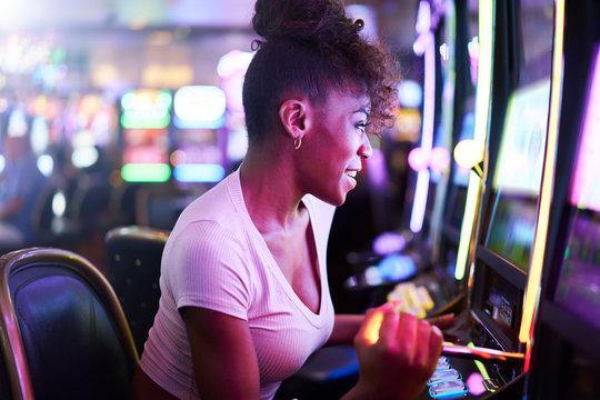 woman having fun playing slot machine at casino