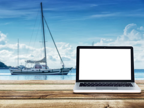 computer laptop with blank white screen on wooden table with yacht boats floating on the sea at background. Travel vacation concept.