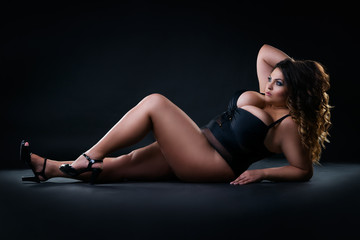 Plus size sexy model in swimsuit, fat woman on black studio background, overweight female body