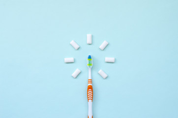 Toothbrush and chewing gums lie on a pastel blue background. Top view, flat lay. Minimal concept