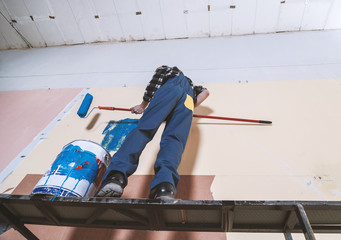 Man painting wall in blue color with paint roller