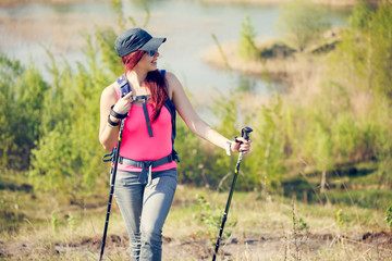 Image of young sporty girl looking away with walking sticks on background of lake and green vegetation