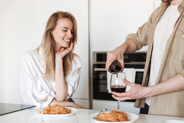 Loving couple in kitchen have a dinner drinking wine eating spaghetti.