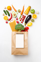 Photo of paper bag with vegetables, fruits and spaghetti . Empty notepad for text