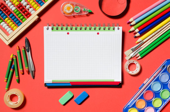 Notepad and school supplies, stationery, red background.