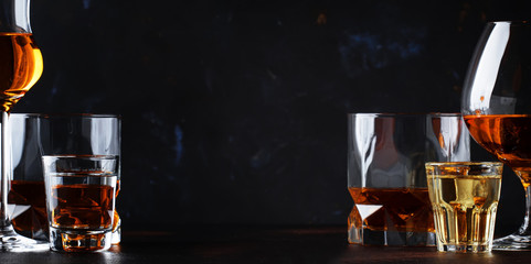 Photo Blinds Bar Set of strong alcoholic drinks in glasses and shot glass in assortent: vodka, rum, cognac, tequila, brandy and whiskey. Dark vintage background, selective focus