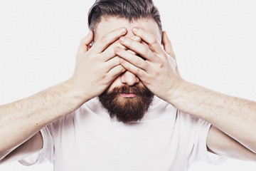 young bearded man closing his eyes over  white  background