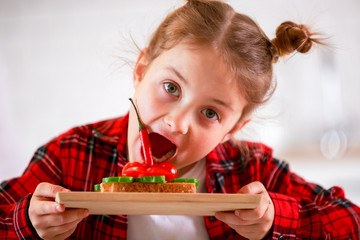 Photo of little girl biting sandwich on white background