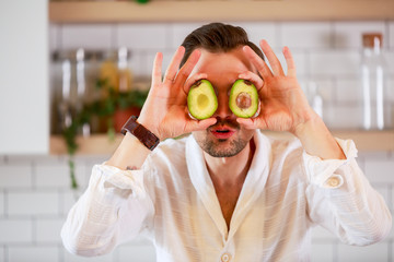 Photo of young man holding avocado near his eyes
