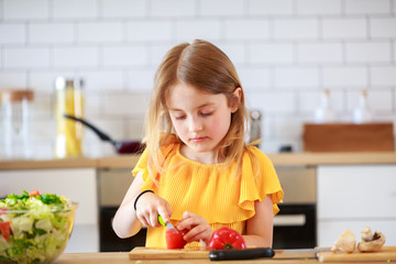 Photo of little girl cutting tomato
