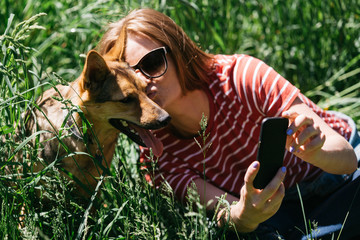 Image of woman doing selfie on walk with dog on green lawn