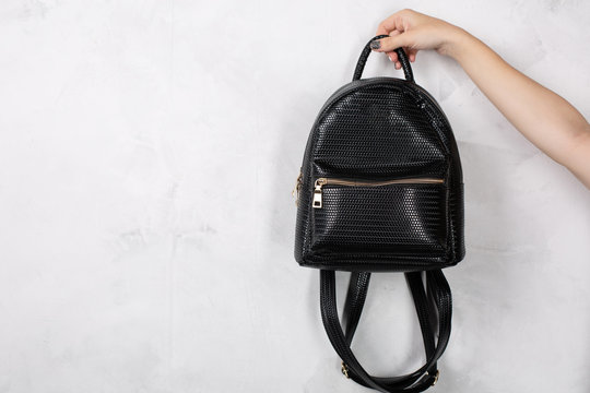 Female hand holding small leather backpack against white wall. Empty space