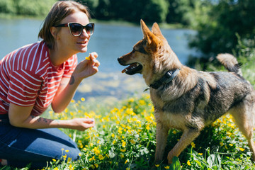 Image of young woman with dog near pond